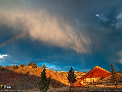 Taken at the Painted Hills National Monument in Central Oregon near sunset. Having been here numerous times before in the summer months, seeing a rainbow on a 100-degree day was the last thing I expected ? usually the skies are clear on hot days.